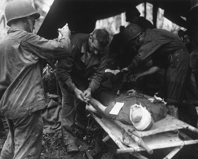 His head bandaged, a wounded Marine on the island of Rendova in the Solomons receives continuing care at an aid station near the front line.