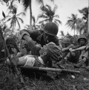 A Navy corpsman gives a drink of water to a wounded Marine on the island of Guam in the Pacific. In addition to the thousands of casualties treated by the U.S. Army medical personnel, the U.S. Navy also trained many for the war effort.
