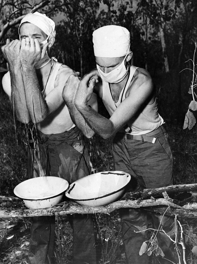 Two Army surgeons scrub up in preparation for a surgical procedure at a first aid station. Although significant advances were made in the treatment of casualties during World War II, conditions were often spartan.
