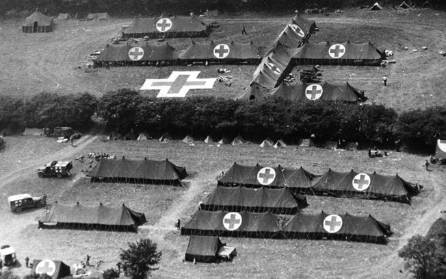 Clearly marked by large red crosses atop its tents, a U.S. Army field hospital has been erected on the Cherbourg Peninsula in France during the summer of 1944. The distinctive markings were placed for easy visual recognition from the air.