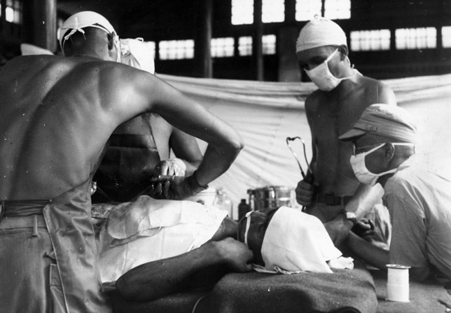An American surgeon and his attending orderlies perform surgery on a wounded Chinese soldier in the recently liberated Chinese city of Kwelin. This operation is taking place at a Portable Surgical Hospital, a facility established in close proximity to the front lines.