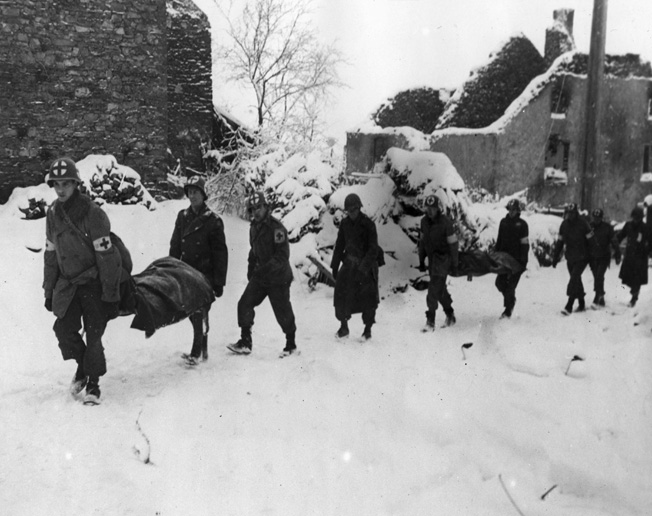 Medical Personnel of the U.S. 35th Infantry Division carry litters of wounded soldiers toward the rear near the snow-covered town of Lutrebois, Belgium.