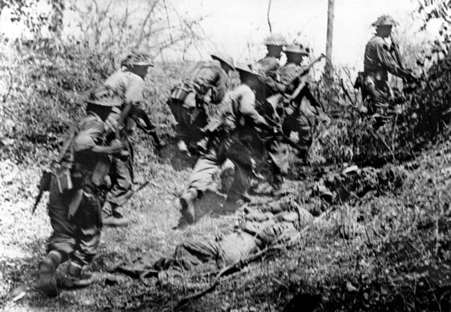 British soldiers move quickly past a dead Japanese soldier in an overrun Japanese position near Yindar, 12 miles from Meiktila, May 1945.
