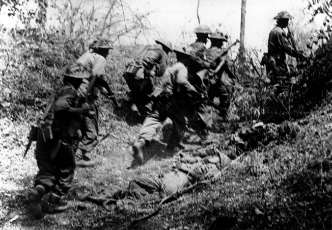 British soldiers advance rapidly through an overrun position formerly occupied by a Japanese sniper near Yindar, 12 miles southeast of Meiktila, May 1945.
