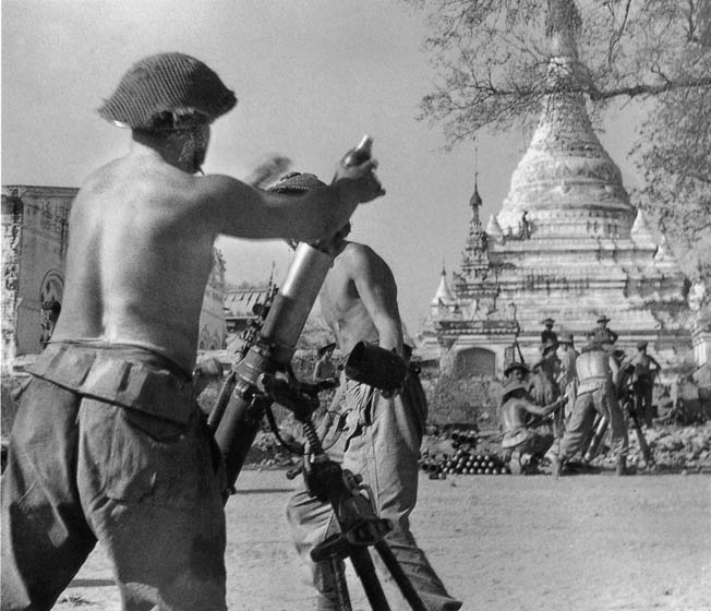 With a sacred pagoda in the background, British mortarmen of the West Yorkshire Regiment (14th Army) shell Japanese positions in Meiktila, February 28, 1945.