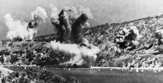 Explosions from Japanese bombs erupt in clouds of dust and debris during an air raid against American and Australian positions at Milne Bay on New Guinea.
