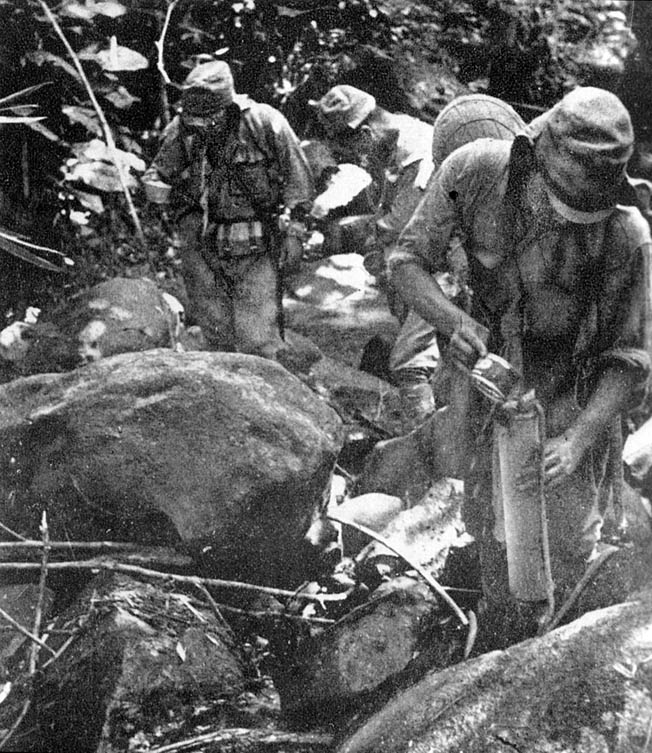 Sweat-drenched Japanese soldiers fill their canteens along the Kokoda Trail during the march on Port Moresby, September 1942. Ill-prepared Allied troops were initially stymied by the Japanese, who fought with more tenacity than expected.