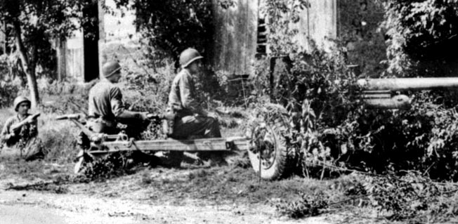 The crew of an American 57mm antitank gun engages the enemy during the Battle of Mortain. Both sides sought to retain Hill 314 east of Mortain because of its value to artillery spotters.