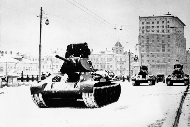 With the front line no more than 20 miles away, newly arrived Soviet tanks roll through the streets of Moscow to bolster the city's defenses.