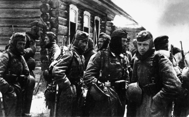 The lack of winter clothing, as seen in this photograph of German troops awaiting orders outside a command post near Moscow in November 1941, hampered the efforts of the Wehrmacht to capture the Soviet capital city.