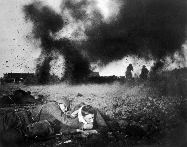 Bursting Soviet artillery shells send shrapnel, earth, and debris raining down on German soldiers near Moscow. The intensity of this bombardment is apparent on the faces of the frightened German soldiers in the foreground.