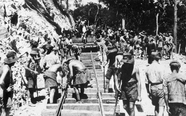 Australian and British prisoners lay track on the Burma-Thailand Railway in sweltering jungle heat. Another group of prisoners, mostly Americans, also labored on the rail line.