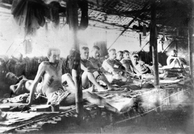 Emaciated Allied prisoners stare blankly at the photographer who snapped this photo of them lying on sleeping platforms in a large POW camp hut.