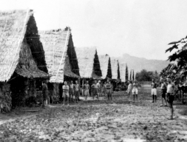 Allied prisoners stand outside their huts at the Nong Pladuk POW camp. Charlie Mott was sent to this camp in September 1942. After the completion of the Burma-Thailand Railway, a number of prisoners were taken to Nong Pladuk. Others boarded Hell Ships for the arduous trek to Japan. The headquarters building of the Japanese camp commander can be seen in the background.