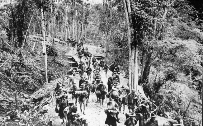 Marching to a new campsite, Allied prisoners of war are relocated to a new area to continue working on the Burma-Thailand Railway. Thousands of prisoners lost their lives working in harsh jungle conditions.