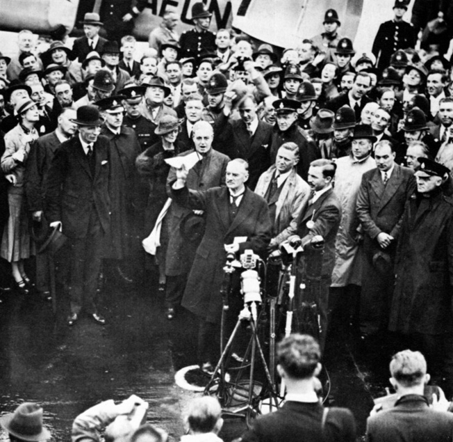 Neville Chamberlain stands in front of a welcoming crowd upon his return from negotiating with Hitler in Munich.
