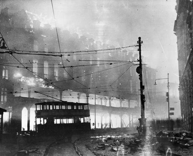 The ruins of a London street continue to burn after a December 14, 1941 raid.