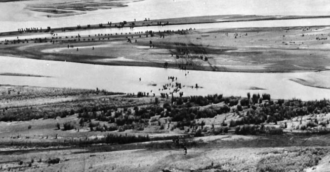 Australian troops of the 2/2nd Pioneer Battalion cross the Markham River along with approximately 800 accompanying natives and engineers of the 2/6th Field Company.