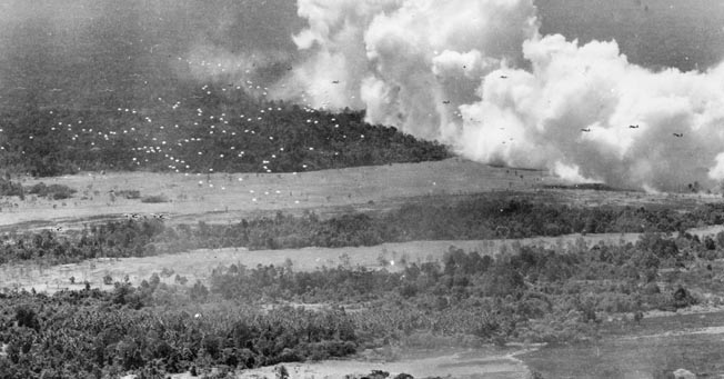 The skies above Nadzab became a beehive of activity as C-47 transport planes were accompanied on their mission by 146 Lockheed P-38 Lightning fighter planes. Some of the fighters flew close to the C-47s while others flew top cover at higher altitude. One of two groups of C-47s in this image approaches its drop zone from 15,000 feet.
