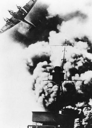 A German Me-110 fighter streaks over a smoking German destroyer during the intense fighting in April 1940.