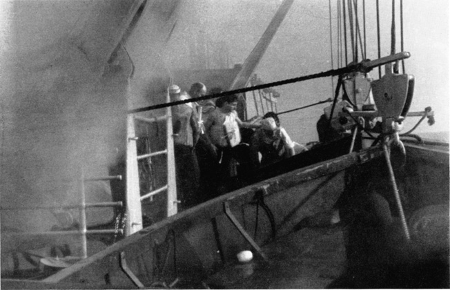 Crewmen of the Belgian freighter Ville de Namur rush to the lifeboats after their vessel has taken a torpedo hit from a prowling German submarine.