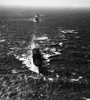 Escorted by warships of the U.S. Navy, a convoy bound for the hazardous Atlantic shipping lanes and Great Britain leaves the harbor at Brooklyn, New York, in 1941.