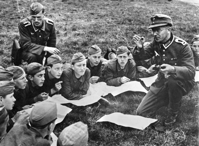 The Nazis began indoctrinating children to their ideology and in service to the militaristic state at an early age. In this photo, boys of the Hitler Youth listen to an instructor on the proper use of the compass during an orienteering exercise. By the time World War II broke out, the Hitler Youth had produced thousands of young, fanatical Nazi soldiers.