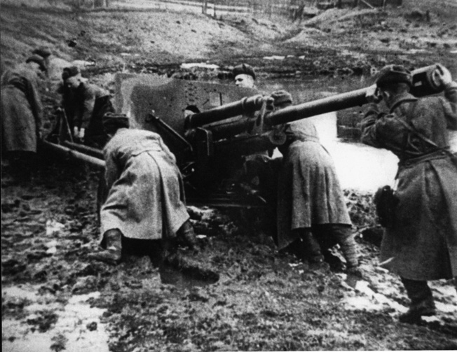 """Wheeling a field artillery piece into position, Soviet soldiers begin the famous """"mud offensive"""" against the German salient at Korsun on the Dnieper River. The offensive was directed by General Ivan Konev."""