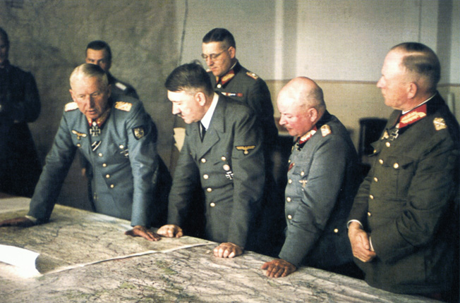 During a visit to the field headquarters of Army Group South on February 19, 1943, Hitler and his field marshals confer over a map of the current tactical situation. From left, the group includes, Field Marshal Erich von Manstein, Hitler, Field Marshal Theodor Busse.