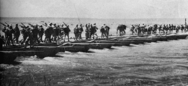Japanese troops cross the Halha River into Mongolian territory on a pontoon bridge.