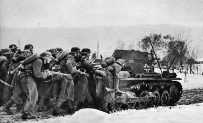 Crouching behind a Panzer I, German infantrymen advance during an assault on a Norweigan village, April 1940.