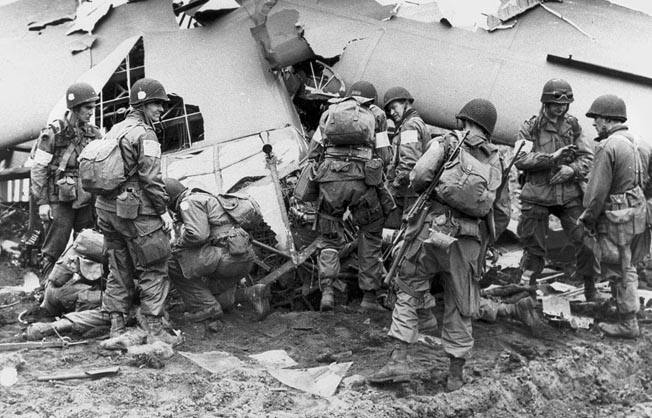 Paratroopers of the 101st Airborne Division, who have recently jumped into Holland during Operation Market Garden in September 1944, inspect the wreckage of a glider that has crashed on landing.