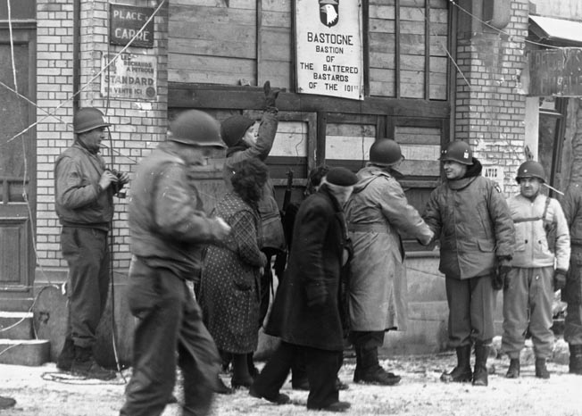Officers greet one another after the raising of the siege of Bastogne during the Battle of the Bulge. Bastogne was a vital crossroads town that was held against the Germans at a crucial period during the battle. Norwood Thomas spent several days in a hospital in the town before returning to combat.