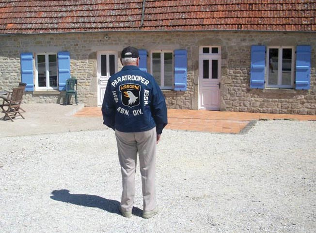 During a return trip to Normandy, Norwood Thomas stands in front of the bar in Pouppeville, France, where he stopped on D-Day. The building has since been converted into a residence.