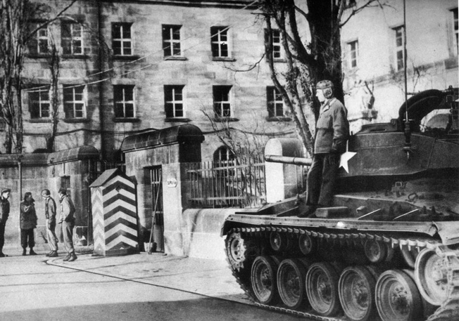 A U.S. tank and a number of infantrymen guard the entrance to the Palace of Justice at Nuremberg. Concerns over disruptions of the trials of accused Nazi war criminals prompted tight security during the proceedings.