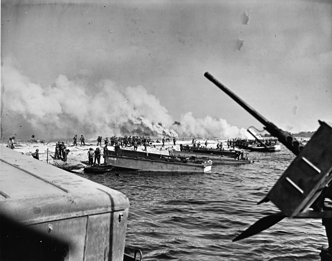 Smoke pots billow a covering pall as troops of the U.S. 15th Infantry Regiment come ashore from their LCVPs (Landing Craft Vehicle, Personnel) at approximately 8:30 am on August 15, 1944.
