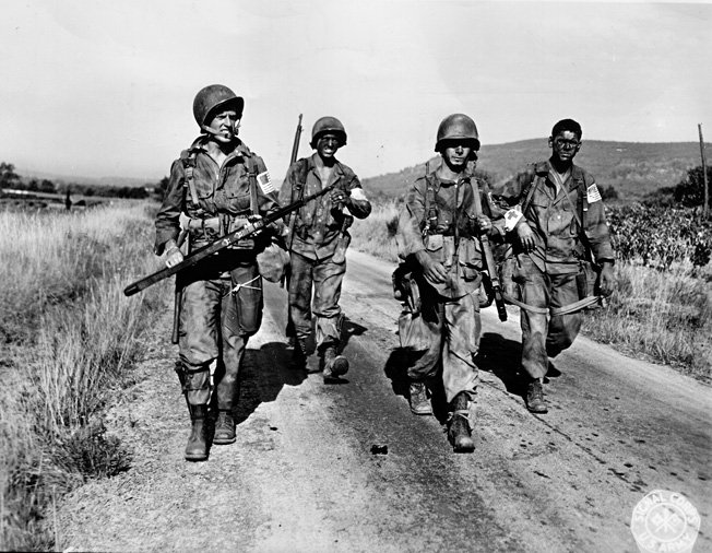Near the French town of Le Muy, American paratroopers of the 509th Parachute Infantry Battalion hurry down Route D7 on the morning of August 15, 1944.