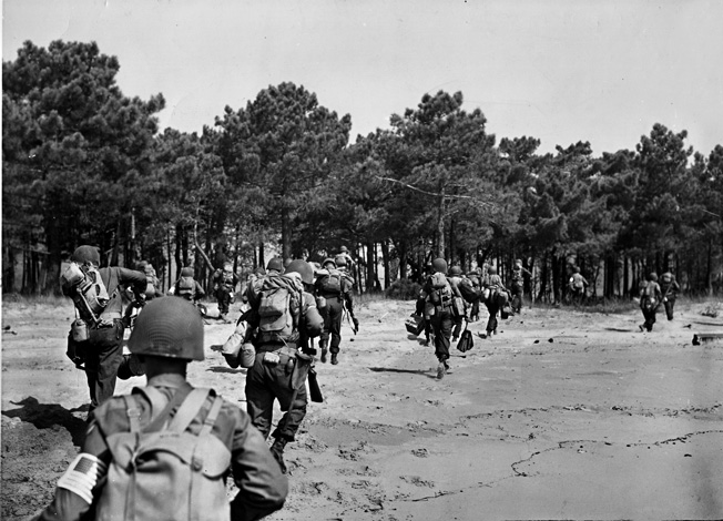 Hustling off the beach on the morning of August 15, 1944, American soldiers have just set foot in France during Operation Anvil-Dragoon. The cover of a nearby pine grove will serve as an area for orientation and rallying troops to their various commands.