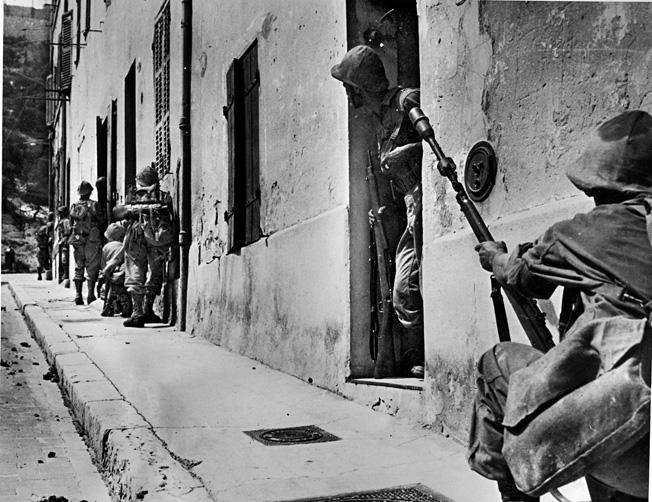 Advancing cautiously through the streets of the city of Marseilles, Algerian troops keep an eye out for German snipers near the Notre Dame-de-la-Garde basilica on August 28, 1944, two weeks after the initial Allied landings in Southern France. The soldier in the foreground has affixed a rifle grenade to his weapon.