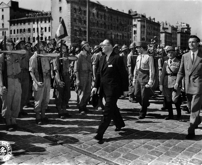 Dignitaries and French officers review troops assembled in the city after the liberation of Marseilles. General Jean de Lattre de Tassigny, commander of the French Army's 2nd Corps, walks second from right in the procession.