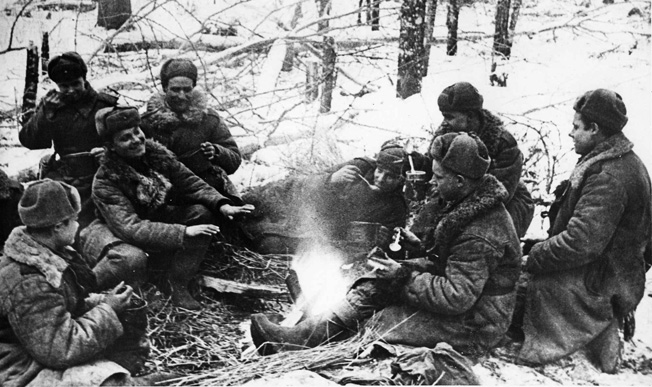Uniformed against the cold, soldiers of the Red Army gather around a campfire during a lull in fighting on the Eastern Front.