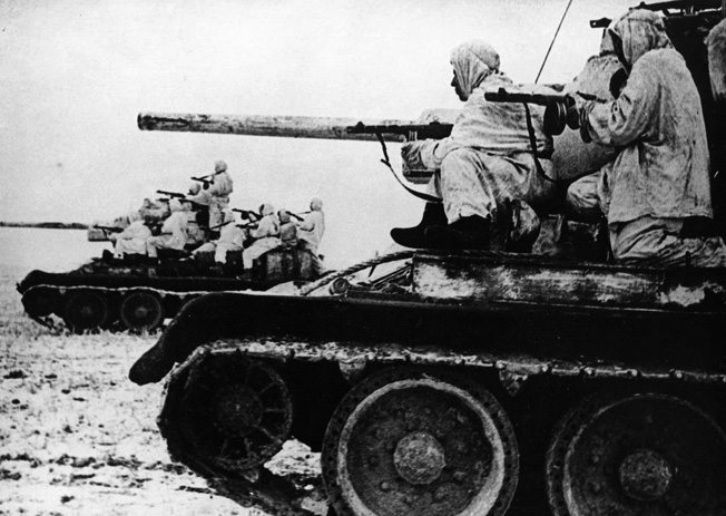 Assuming the offensive, Red Army soldiers exploit a breakthrough in the German lines as they ride aboard Soviet T-34 tanks.