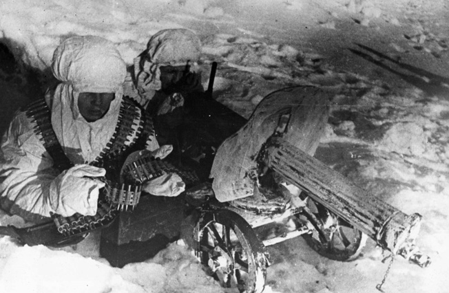 Wearing hooded camouflage uniforms, a pair of Red Army soldiers fires an antiquated machine gun at German positions. The winter weather created a no-man's-land of snow and ice between opposing lines.