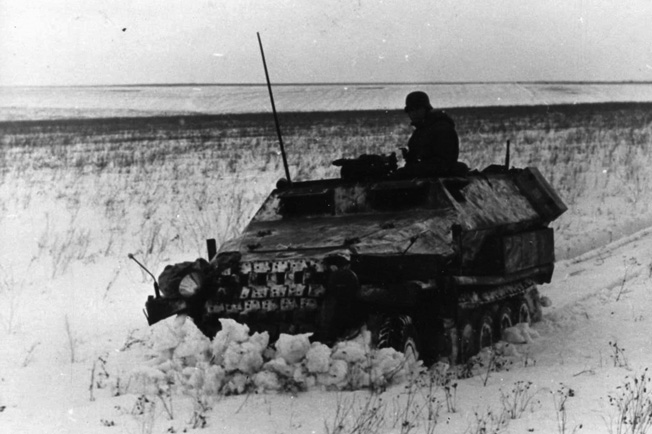 Battling the intense cold and winter weather as well as the Red Army, a German patrol and its armored half-track forge their way through a snowy field on the Russian steppe during the winter of 1942.