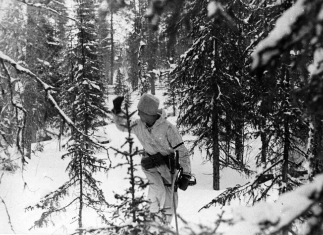 Motioning to his troops to follow quickly, a German soldier leads a detachment through a wooded area of Russia. The winter weather took a heavy toll on the unprepared Germans.