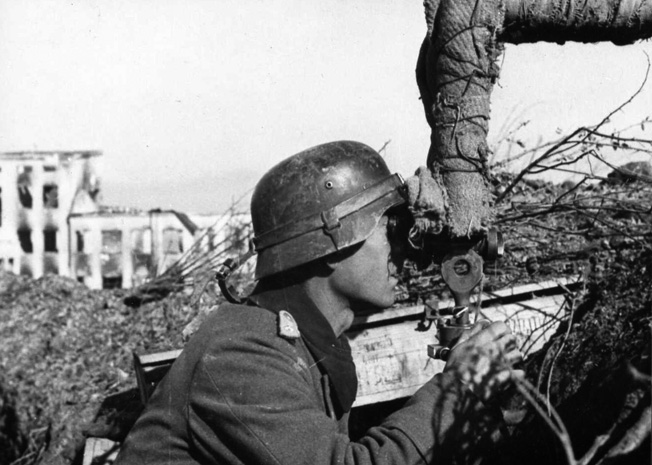 During the catastrophic German defeat at Stalingrad, a Wehrmacht soldier peers from cover through a telescopic viewer. The distant Soviet Red Army tightened the ring of steel around the Germans at Stalingrad until they capitulated in February 1943.