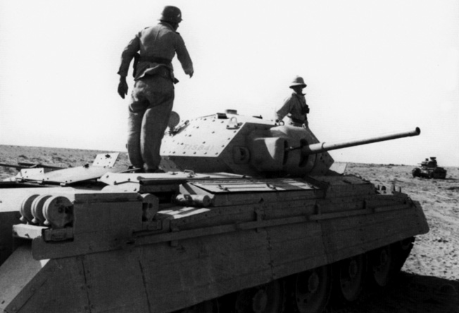 Captured with the fall of Bir Hacheim in North Africa, a Crusader tank is inspected by German troops. Practically in tact, this vehicle was also taken with plenty of ammunition to turn against its original owner.