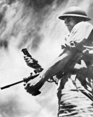 An Australian soldier demonstrates the  firing of the Owen gun. The Owen gun took a  circuitous path to approval and production but eventually reached frontline troops and more than 50,000 were manufactured.
