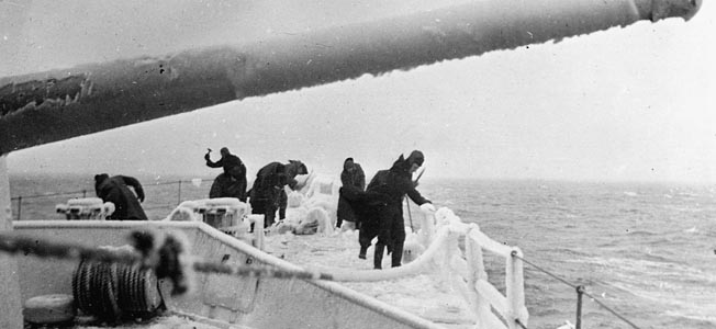 Crew members attempt to clear the ice from the frozen deck of their destroyers.
