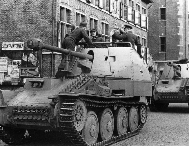 Crewmen scramble around the turret of a Marder III as the vehicle prepares to move out of the close quarters of an occupied town. THe Marder was not well suited to urban combat.